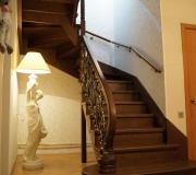 Деревянная лестница в загородном доме. Лестница на второй этаж с металлическими балясинами.