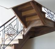 Деревянная лестница на второй этаж с кованным ограждением.