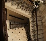 Монолитная лестница с комбинированным ограждением из дерева и металлических балясин