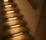 Лестница в загородном доме на металлическом каркасе с подсветкой.